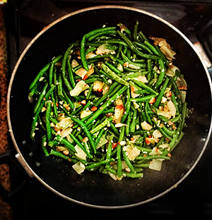 Green beans and almonds simmer in a wok on the stove.