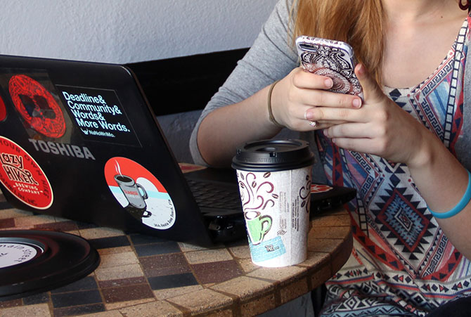 A girl checks her phone while using her laptop in a coffee shop.