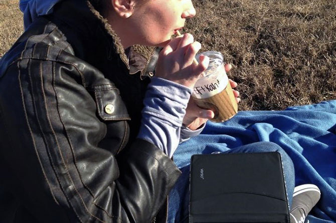 A woman sips coffee on a blanket outside with her tablet in her lap.